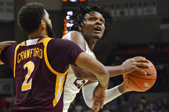Connecticut's Josh Carlton, right, looks to shoot as Iona's E.J. Crawford, left, defends, in the second half of an NCAA college basketball game, Wednesday, Dec. 4, 2019, in Storrs, Conn. (AP Photo/Jessica Hill)
