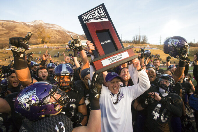 FILE - In this Nov. 18, 2017, file photo, Weber State coach Jay Hill hoists the trophy after they defeated Idaho State in an NCAA college football game for a share of the Big Sky Conference title in Ogden, Utah. The The Big Sky Conference postponed its football season on Friday, Aug. 7, 2020, to the spring because of the coronavirus pandemic and called for the FCS playoffs to be moved to the second semester as well. (Matt Herp/Standard-Examiner via AP, File)
