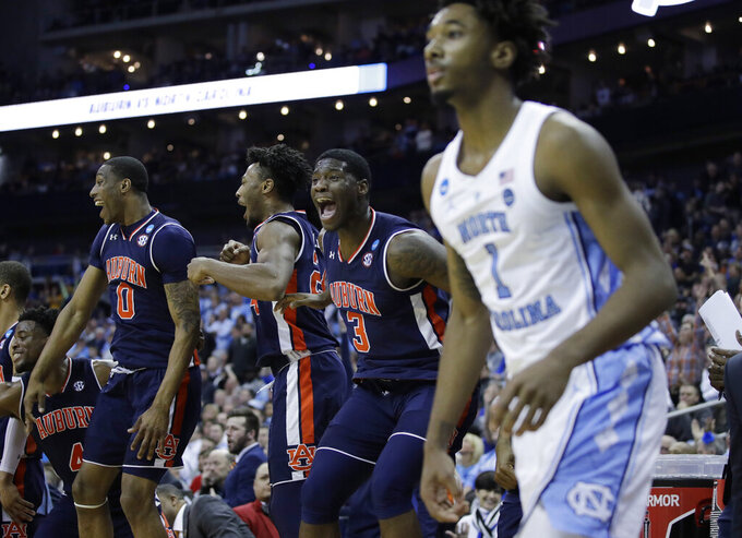 Auburn's Horace Spencer (0), left, Anfernee McLemore, Danjel Purifoy (3) celebrate alongside North Carolina's Leaky Black (1) near the end of a men's NCAA tournament college basketball Midwest Regional semifinal game Friday, March 29, 2019, in Kansas City, Mo. (AP Photo/Charlie Riedel)