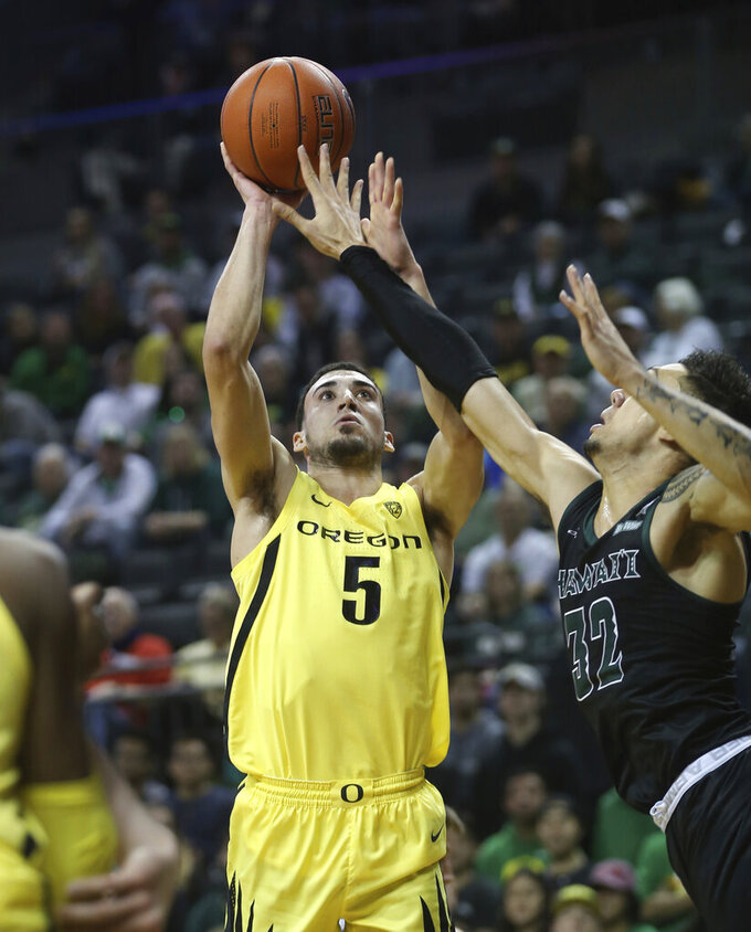 Oregon's Chris Duarte shoots over Hawaii's Samuta Avea, right, during the first half of an NCAA college basketball game in Eugene, Ore., Saturday, Dec. 7, 2019. (AP Photo/Chris Pietsch)