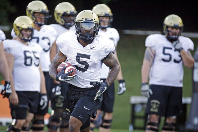In this Aug. 5, 2019, photo, Vanderbilt running back Ke'Shawn Vaughn (5) runs a drill during an NCAA college football practice in Nashville, Tenn. Vanderbilt has won at least five games each of the past three seasons and reached two bowls in that span. They've also won three straight against in-state rival Tennessee for their longest winning streak in this series since the 1920s. (AP Photo/Mark Humphrey)