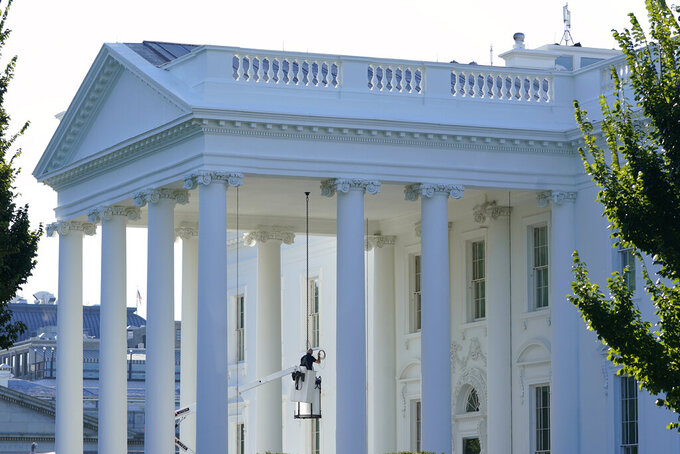 A worker works on the light fixture over the North Portico of the White House in Washington, Friday, Sept. 3, 2021. (AP Photo/Susan Walsh)