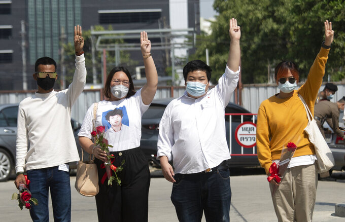 Pro-democracy activists, from left, Panupong Jadnok, Panusaya Sithijirawattanakul, Parit Chiwarak, and Benja Apan, gesture with a three-fingers salute, a symbol of resistance as they walk to Pathumwan police station in Bangkok, Thailand, Wednesday, Jan. 20, 2021. Six pro-democracy activists, including two 17-year old minors, report to police after being issued summonses to answer charges of lese majeste or defaming or insulting key members of the royal family. (AP Photo/Sakchai Lalit)