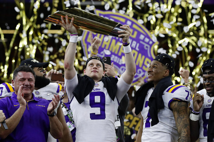FILE - In this Monday, Jan. 13, 2020, file photo, LSU quarterback Joe Burrow holds the trophy as safety Grant Delpit looks on after LSU defeated Clemson 42-25 in the NCAA College Football Playoff national championship game, in New Orleans. Imagine if a pandemic had shortened or wiped out that last, golden season for Burrow, who won the Heisman Trophy and led LSU to the national championship. Would he still have emerged as the first overall NFL draft pick? (AP Photo/Sue Ogrocki, File)
