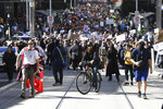 Hundreds of protesters march on a street during an anti-lockdown protest in Melbourne, Australia, Saturday, Aug. 21, 2021. Protesters are rallying against government restrictions placed in an effort to reduce the COVID-19 outbreak. (James Ross/AAP Image via AP)
