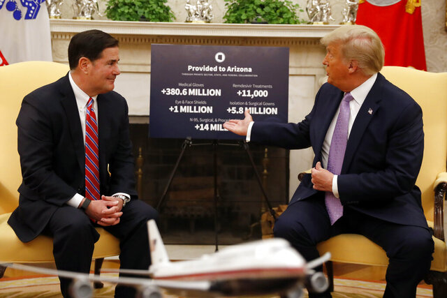 FILE - In this Aug. 5, 2020 file photo, President Donald Trump meets with Arizona Gov. Doug Ducey, neither wearing masks, in the Oval Office of the White House in Washington. In early August, Ducey beamed in the White House as he basked in praise from Trump for his handling of the COVID-19 outbreak. Arizona's response to the virus, Trump said, was a model for other states. Just a few weeks earlier, Ducey was being vilified as Arizona hospital beds filled with infected patients and hundreds of people were dying each week as cases in Arizona spiked. Whether Ducey deserves credit or blame for alternately controlling and unleashing the virus is not in doubt — observers say he's earned both. (AP Photo/Andrew Harnik, File)