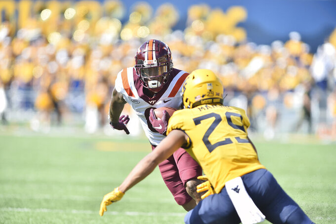 Virginia Tech running back Jalen Holston (0) slips a tackle by West Virginia Mountaineers safety Sean Mahone (29) during the second half of an NCAA college football game in Morgantown, W.Va., Saturday, Sep. 18, 2021. (AP Photo/William Wotring)