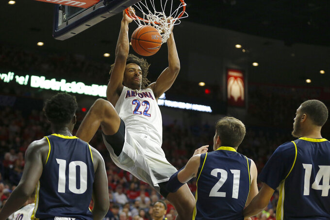 Arizona forward Zeke Nnaji (22) dunks over Northern Arizona's Bernie Andre (10), Luke Avdalovic (21) and Isaiah Lewis (14) during the second half of an NCAA college basketball game Wednesday, Nov. 6, 2019, in Tucson, Ariz. (AP Photo/Rick Scuteri)