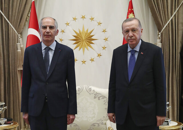 FILE - In this Aug. 19, 2020 file photo, Frence ambassador to Turkey Herve Magro, left, and Turkey's President Recep Tayyip Erdogan pose for photographs after the new ambassador presented his letter of credentials, in Ankara, Turkey. France recalled its ambassador to Turkey for consultations after Erdogan said Saturday, Oct. 24 French President Emmanuel Macron needed mental health treatment and made other comments that the French government described as unacceptably rude.(Turkish Presidency via AP, Pool)