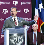 FILE - In this June 3, 2019, file photo, Texas A&M athletic director Ross Bjork, left, addresses media and A&M athletic staff in the Hall of Champions in College Station, Texas, as interim athletic director R.C. Slocum, right, looks on. The scheduled start of college football season is fewer than three months away, and there are plenty of reasons to be hopeful that games will be played Labor Day weekend. Texas A&M athletic director Ross Bjork said the school has conducted just under 500 COVID-19 tests on coaches, staff and athletes since May 18. The Pac-12 is the only major college football conference in which all the members have agreed to test all returning athletes for COVID-19. (Dave McDermand/College Station Eagle via AP, File)