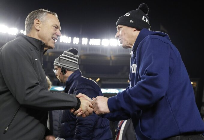 Michigan State head coach Mark Dantonio, left, shakes hands with Pro Football Hall of Fame quarterback Jim Kelly, right, during the second half of the Pinstripe Bowl NCAA football game Friday, Dec. 27, 2019, in New York. (AP Photo/Frank Franklin II)