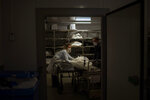 Mortuary workers Marina Gómez and Manel Rivera store the body of a person who died of COVID-19 at Mémora morgue in Barcelona, Spain, Thursday, Nov. 5, 2020. Gómez and her fellow mortuary workers form part of Spain's rarely seen front line in the fight against COVID-19. Like doctors and nurses, they are part of a group of essential workers who see and touch the daily march of death amid the worst public health crisis in over a century. (AP Photo/Emilio Morenatti)