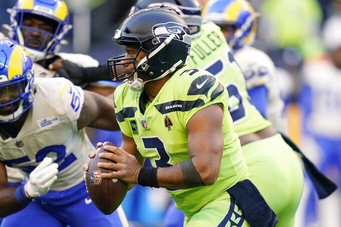 Seattle Seahawks quarterback Russell Wilson looks to pass against the Los Angeles Rams during the first half of an NFL football game, Thursday, Oct. 7, 2021, in Seattle. (AP Photo/Elaine Thompson)