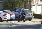Fresno police investigators work near the driveway where a shooting took place at a house party which involved multiple fatalities and injuries in Fresno, Calif., Monday, Nov. 18, 2019. (AP Photo/Gary Kazanjian)