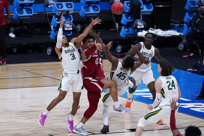 Arkansas forward Justin Smith (0) passes between Baylor guard MaCio Teague (31) and 1guard Davion Mitchell (45) during the second half of an Elite 8 game in the NCAA men's college basketball tournament at Lucas Oil Stadium, Monday, March 29, 2021, in Indianapolis. (AP Photo/Michael Conroy)
