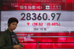A man walks past an electronic board showing Hong Kong share index outside a bank in Hong Kong, Thursday, Feb. 14, 2019. Asian stocks were mostly lower on Thursday as China and the U.S. kicked off two days of trade negotiations in Beijing. (AP Photo/Kin Cheung)