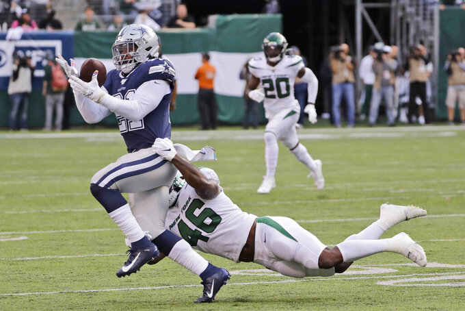 New York Jets' Neville Hewitt, right, tries to bring down Dallas Cowboys' Ezekiel Elliott during the first half of an NFL football game, Sunday, Oct. 13, 2019, in East Rutherford, N.J. (AP Photo/Frank Franklin II)