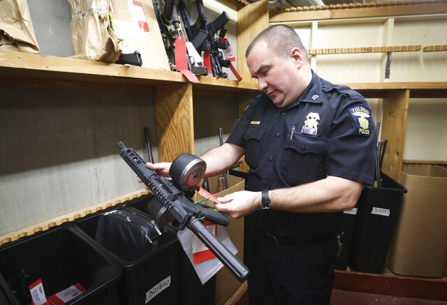 In this Monday, Nov. 4, 2019 photo, Sgt. Ed Mack looks at a pistol in an evidence room at the Toledo Police Department, in Toledo, Ohio. In the basement of the Toledo Police Department, more than 20,000 items collected from crime scenes across the city each year are stored to help verify what happened or to be used to find and convict suspects.  (Andy Morrison/The Blade via AP)