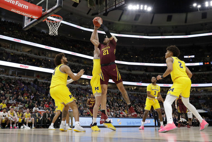 Minnesota's Jarvis Omersa (21) takes a shot against Michigan's Colin Castleton during the first half of an NCAA college basketball game in the semifinals of the Big Ten Conference tournament, Saturday, March 16, 2019, in Chicago. (AP Photo/Nam Y. Huh)