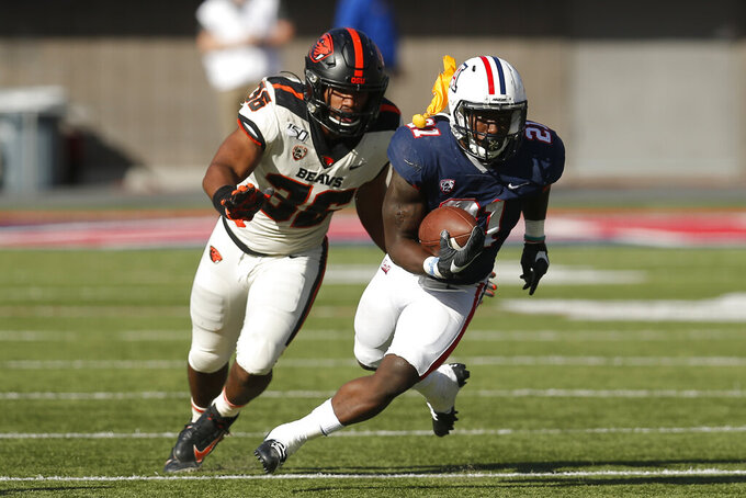 /a21o/ runs away from Oregon State linebacker Omar Speights (36) as a referee's' flag hits him in the shoulder pads in the first half during an NCAA college football game, Saturday, Nov. 2, 2019, in Tucson, Ariz. (AP Photo/Rick Scuteri)