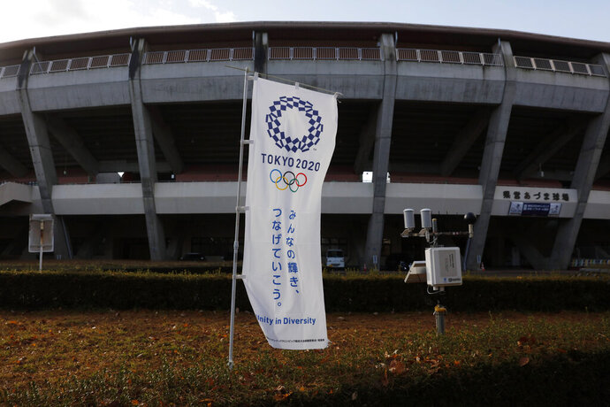 A Tokyo 2020 banner stands in front of the Azuma Baseball Stadium, a venue for baseball and softball at the Tokyo 2020 Olympics, Saturday, Nov. 30, 2019, in Fukushima, Fukushima prefecture, Japan. The torch relay for the Tokyo Olympics will kick off in Fukushima, the northern prefecture devastated almost nine years ago by an earthquake, tsunami and the subsequent meltdown of three nuclear reactors. (AP Photo/Jae C. Hong)