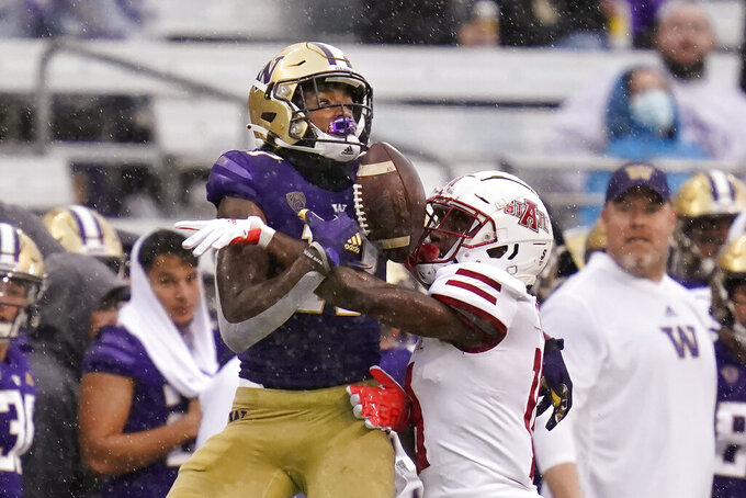 Washington's Taj Davis, left, is tightly defended by Arkansas State's Denzel Blackwell in the first half of an NCAA college football game, Saturday, Sept. 18, 2021, in Seattle. Davis made the catch on the play. (AP Photo/Elaine Thompson)