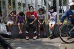 Children wait for a meal from the mobile dining rooms program as people who have not been able to work because of the COVID-19 pandemic line up for a meal outside the Iztapalapa hospital in Mexico City, Wednesday, May 20, 2020. (AP Photo/Marco Ugarte)
