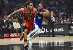 Atlanta Hawks guard Trae Young, left, receives an inbound pass while Los Angeles Clippers guard Rodney McGruder defends during the first half of an NBA basketball game in Los Angeles, Saturday, Nov. 16, 2019. (AP Photo/Kelvin Kuo)