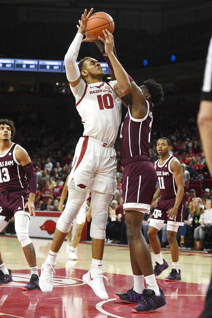 Arkansas forward Daniel Gafford (10) shoots over Texas A&M defender Christian Mekowulu (21) during the first half an NCAA college basketball game, Saturday, Feb. 23, 2019, in Fayetteville, Ark. (AP Photo/Michael Woods)