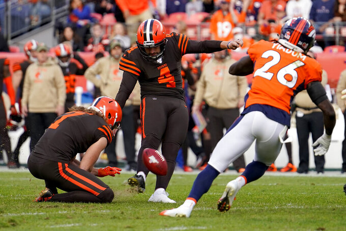 Cleveland Browns kicker Austin Seibert (4) kicks a field goal as punter Jamie Gillan (7) holds as Denver Broncos cornerback Isaac Yiadom (26) defends during the first half of NFL football game, Sunday, Nov. 3, 2019, in Denver. (AP Photo/Jack Dempsey)