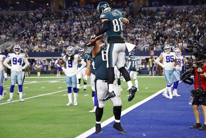 Philadelphia Eagles' Landon Dickerson, center left, and Zach Ertz (86) celebrate Ertz' touchdown catch in the second half of an NFL football game against the Dallas Cowboys in Arlington, Texas, Monday, Sept. 27, 2021. (AP Photo/Ron Jenkins)