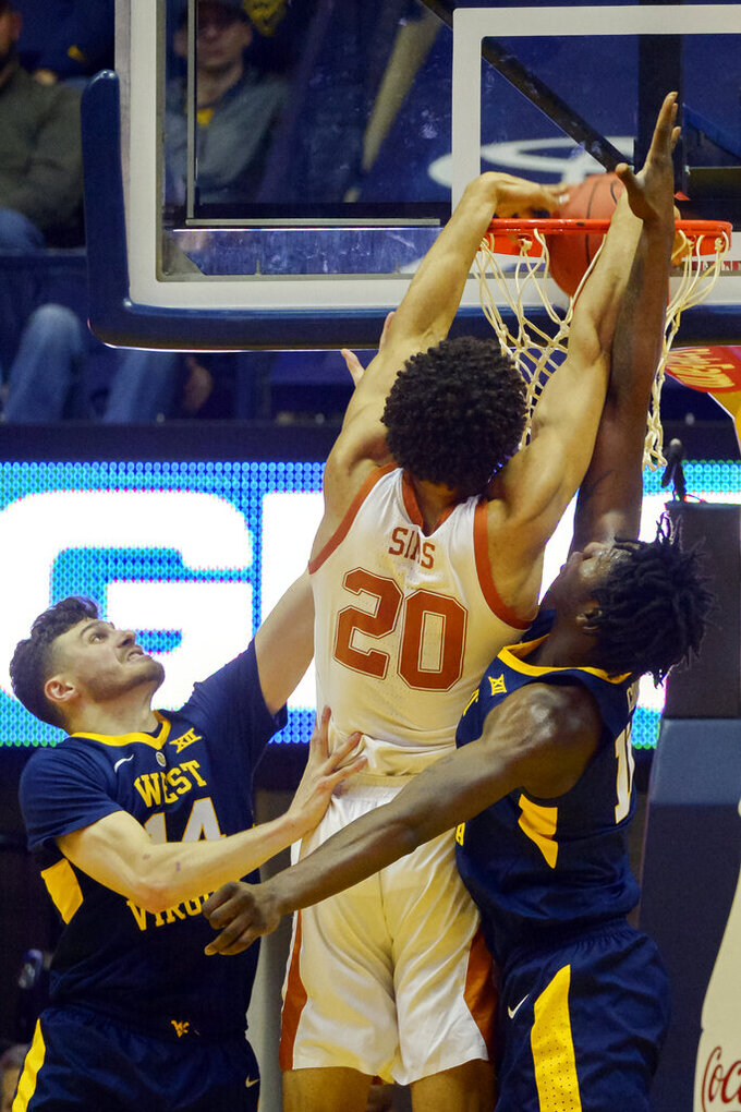 West Virginia guard Chase Harler (14) and  forward Andrew Gordon (12) fail to block Texas forward Jericho Sims (20) from a slam dunk during the second half of an NCAA college basketball game in Morgantown, W.Va., Saturday, Feb. 9, 2019. (AP Photo/Craig Hudson)