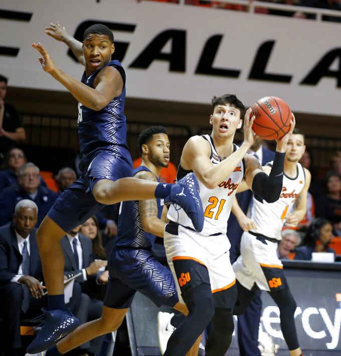 Oklahoma State's Lindy Waters III (21) attempts a shot beside Georgetown's Myron Gardner (15) during an NCAA college basketball game Wednesday, Dec. 4, 2019, in Stillwater, Okla. (Bryan Terry/The Oklahoman via AP)