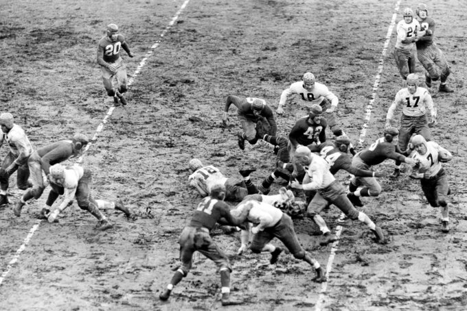FILE - In this Nov. 20, 1938, file photo, Green Bay Packers Ed Jankowski (7), far right, runs after taking the handoff from Cecil Isbell (17) on a reverse as New York Giants Ken Lunday (5) reaches out on an attempted tackle, at the Polo Grounds in New York. The Giants defeated the Packers 15-3.  Jankowski is following teammate and blocker Henry Bruder (5). The Giants player in the foreground is Jim Lee Howell (21). The Packers won four titles in the 1930s, including the first two of the decade _ capping a run of three straight _ when they finished with the league's best record. Green Bay also won in 1936 and '39. (AP Photo/File)