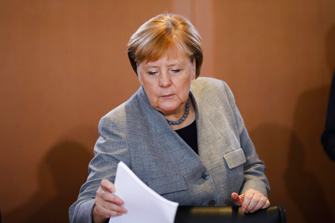 German Chancellor Angela Merkel takes some documents as she arrives for the weekly cabinet meeting of the German government at the chancellery in Berlin, Wednesday, Jan. 15, 2020. (AP Photo/Markus Schreiber)