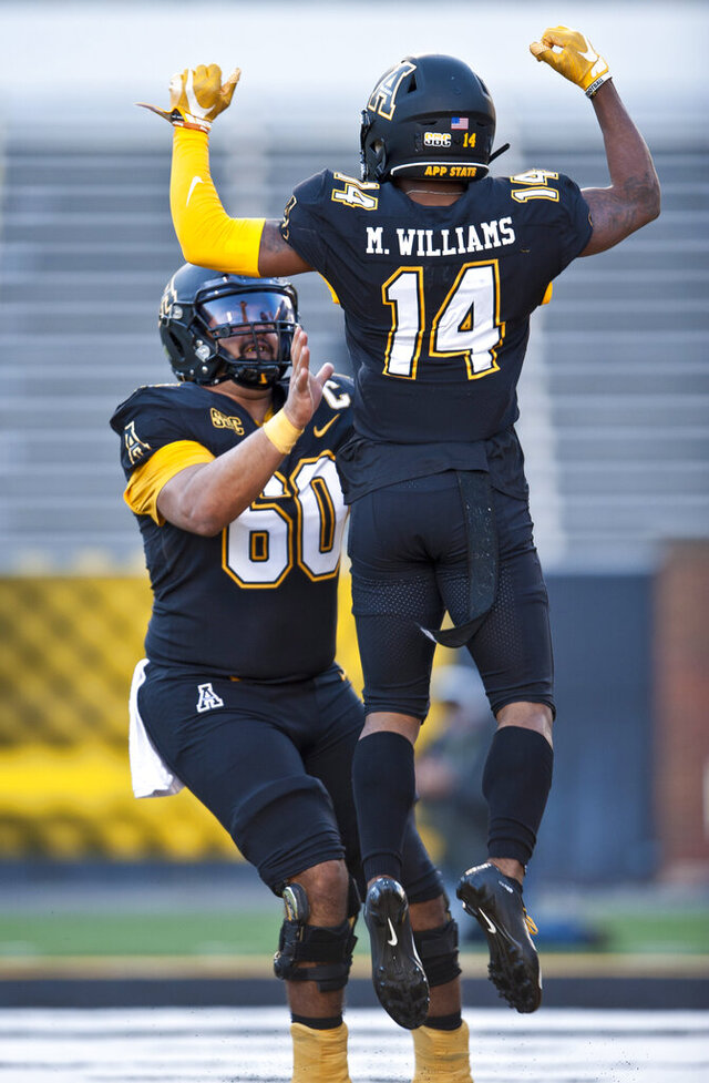 Appalachian State center Noah Hannon (60) and wide receiver Malik Williams celebrate Williams touchdown reception against Troy in the first half of an NCAA college football game Saturday, Nov. 28, 2020, in Boone, N.C. (Walt Unks/The Winston-Salem Journal via AP)