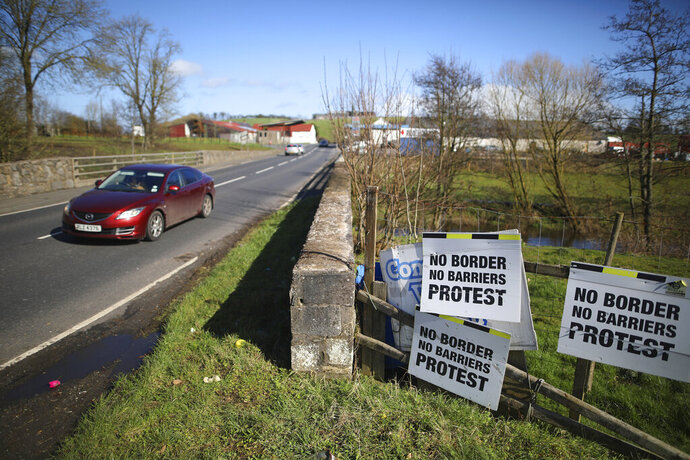 FILE - In this file photo dated Tuesday, March, 12, 2019, a Motorist crosses the Irish border in Middletown, Northern Ireland.  The hope of Britain's Brexit split from the European Union depends on finding a political solution to avoid having a hard border across the peaceful green fields that span the seamless border dividing Britain's Northern Ireland from Europe's Republic of Ireland. (AP Photo/Peter Morrison, FILE)