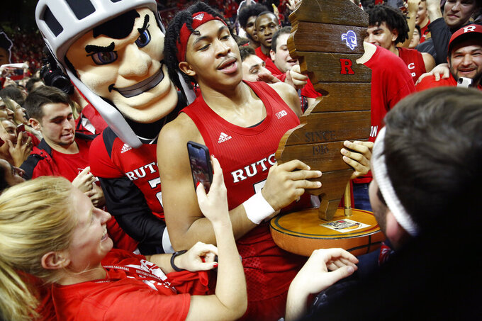 "Fans gather around the Rutgers mascot ""The Scarlet Knight,"" above left, as he stands behind Rutgers guard Ron Harper Jr. who holds the Garden State Hardwood Classic trophy after upsetting Seton Hall in an NCAA college basketball game, Saturday, Dec. 14, 2019, in Piscataway, N.J. Rutgers defeated Seton Hall 68-48. (AP Photo/Kathy Willens)"