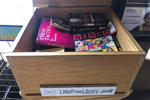 In this April 21, 2020, photo, a full little free library sits outside of a grocery store in Placitas, N.M. Across the United States, volunteers are reporting a jump in usages of official and unofficial tiny popups known as little free libraries as readers look to pass the time amid COVID-19 health restriction. From the American Southwest to New England, little free libraries made of wood or brick, placed in front of parks or in the trunk of a car, have seen their small spaces overwhelmed with books. (AP Photo/Russell Contreras)