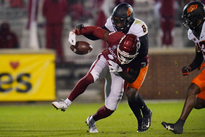 Oklahoma tight end Mikey Henderson (3) loses the ball as he is hit by Oklahoma State cornerback Rodarius Williams (8) during the second half of an NCAA college football game in Norman, Okla., Saturday, Nov. 21, 2020. Oklahoma retained possession. (AP Photo/Sue Ogrocki)