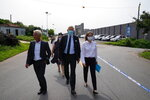 Dominic Barton, Ambassador of Canada to China, center, arrives at a detention center to meet Canadian Michael Spavor, in Dandong, China, Wednesday, Aug. 11, 2021. A Chinese court has sentenced Michael Spavor to 11 years on spying charges in case linked to Huawei. (AP Photo/Ng Han Guan)