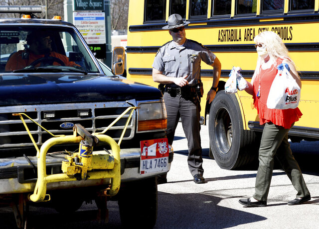 Ohio State Highway Patrol Sgt. Larry Johnson, left, assists Ashtabula Area City Schools employees, including, Tina McCoy at a meal delivery site along Route 20 in Ashtabula, Ohio, on Thursday April 2, 2020, morning. (Warren Dillaway/The Star-Beacon via AP)