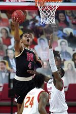 Nebraska guard Shamiel Stevenson (4) goes up for a shot against Maryland guard Darryl Morsell (11) during the second half of an NCAA college basketball game, Tuesday, Feb. 16, 2021, in College Park, Md. Maryland's Donta Scott (24) looks on. Maryland won 64-50. (AP Photo/Julio Cortez)