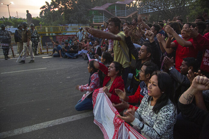 Protesters block a road during a curfew in Gauhati, India, Thursday, Dec. 12, 2019. Police arrested dozens of people and enforced a curfew Thursday in several districts in India's northeastern Assam state where thousands protested legislation that would grant citizenship to non-Muslims who migrated from neighboring countries. (AP Photo/Anupam Nath)