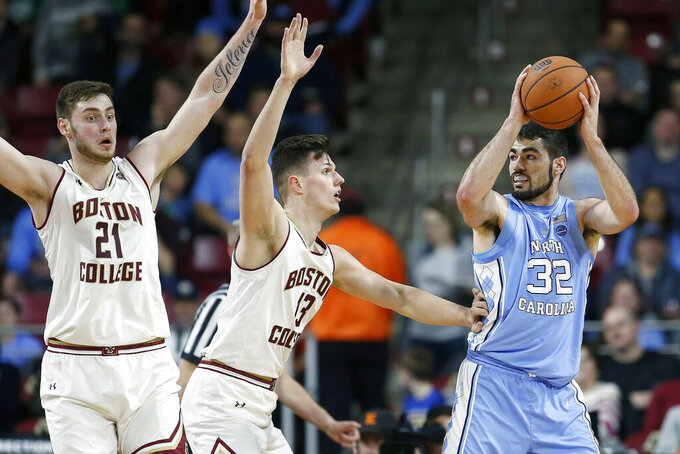 Boston College's Nik Popovic (21) and Luka Kraljevic (13) defend against North Carolina's Luke Maye (32) during the first half of an NCAA college basketball game in Boston, Tuesday, March 5, 2019. (AP Photo/Michael Dwyer)