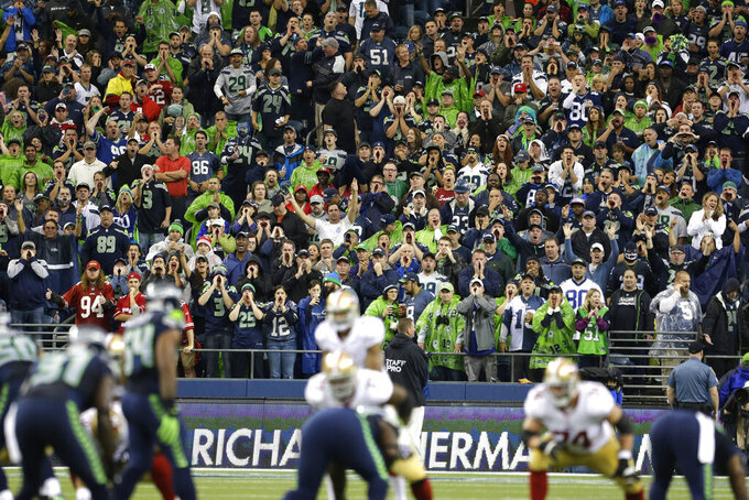 FILE - In this Sunday, Sept. 15, 2013, file photo, Seattle Seahawks fans yell during a San Francisco 49ers possession in the first half of an NFL football game in Seattle. Fans were attempting to set a Guinness World Record for fan noise.  One of the best homefield advantages in the NFL will sit empty on Sunday night, Sept. 20, 2020. . The Seattle Seahawks know it will be strange having no fans inside CenturyLink Field. But being an opponent in Seattle has gained such a reputation even some Patriots are disappointed there won't be fans.  (AP Photo/Elaine Thompson, File)