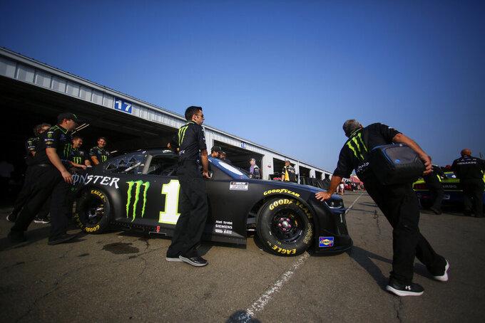 Pit crews push Kurt Busch's car through the garage area before a NASCAR Cup Series auto race in Watkins Glen, N.Y., on Sunday, Aug. 8, 2021. (AP Photo/Joshua Bessex)