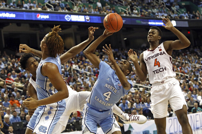 North Carolina guard Brandon Robinson (4) and forward Armando Bacot struggle for a rebound with Virginia Tech guard Nahiem Alleyne (4) and forward John Ojiako, left, during the first half of an NCAA college basketball game at the Atlantic Coast Conference tournament in Greensboro, N.C., Tuesday, March 10, 2020. (AP Photo/Ben McKeown)