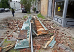 Debris from a storm-damaged building lies in the street in Newburgh, N.Y., Wednesday, May 16, 2018. Powerful storms pounded the Northeast on Tuesday with torrential rain and marble-sized hail, leaving  thousands of homes and businesses without power. (AP Photo/Seth Wenig)