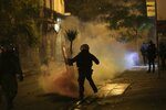 Protesters throw back to riot police a tear gas canister during minor clashes in Athens, Friday, Dec. 6, 2019. Thousands of protesters in Greece have joined marches in the nation's capital and other cities to mark the anniversary of the fatal police shooting of a teenager that sparked extensive rioting 11 years ago. (AP Photo/Yorgos Karahalis)